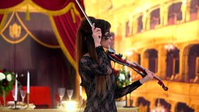 Beautiful young girl playing on electric violin on beautiful concert hall. stock video