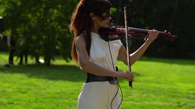 Beautiful young girl playing on electric violin on beautiful park. stock video footage