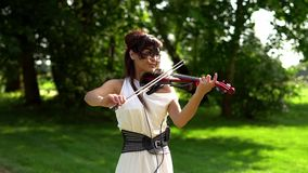 Beautiful young girl playing on electric violin on beautiful park. Sunny, windy day. The violinist smiles.The average plan stock footage