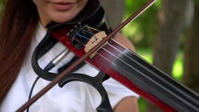 Beautiful young girl playing on electric violin on beautiful park. Sunny, windy day. The violinist smiles. Focus on strings and bow stock video