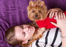 Beautiful young girl playing with her yorkshire terrier at home laying down Royalty Free Stock Photography