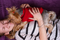 Beautiful young girl playing with her yorkshire terrier at home laying down Stock Image
