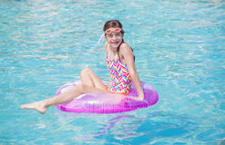 Beautiful young girl playing in the pool in summer time stock photos