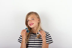 Beautiful young girl playing with two fidget spinners Royalty Free Stock Photography