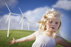 Beautiful Young Girl Playing in Wind Turbine Field. Beautiful Young Girl Playing Near Wind Turbines and Grass Field Royalty Free Stock Images