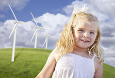 Beautiful Young Girl Playing in Wind Turbine Field. Beautiful Young Girl Playing Near Wind Turbines and Grass Field Royalty Free Stock Photography
