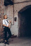 Beautiful Young Girl Plays A Saxophone Standing Near A White Old Wall - Outdoors. Attractive Woman In White Shirt Expression Plays