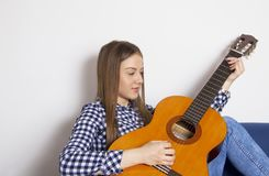 A beautiful young girl plays on an acoustic guitar. Young girl plays on an acoustic guitar.White background.The color of the tree is the guitar stock photo
