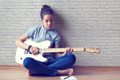 Beautiful young girl plays guitar. Beautiful young girl plays guitar and composes music on a background of a brick wall Royalty Free Stock Images