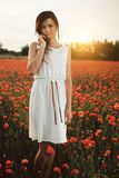 Woman on poppy field. Beautiful young girl on poppy field with dress stock image