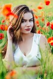 Beautiful young girl in poppy fields at sunset. stock photography