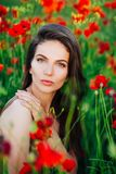 Beautiful young girl in poppy fields at sunset. royalty free stock image