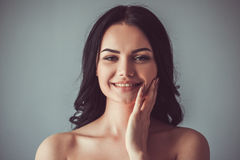 Beautiful young girl. Portrait of beautiful young brunette with bare shoulders touching her cheek, looking at camera and smiling, on gray background Stock Photo