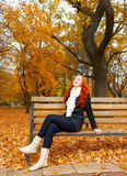 Beautiful young girl portrait sit on bench in park and relax, yellow leaves at fall season, redhead, long hair Royalty Free Stock Photo