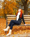 Beautiful young girl portrait sit on bench in park and relax, yellow leaves at fall season, redhead, long hair Royalty Free Stock Photography