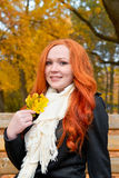 Beautiful young girl portrait sit on bench in park with yellow leaf in hand, fall season, redhead, long hair Royalty Free Stock Photography