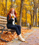 Beautiful young girl portrait sit on bench in park with yellow leaf in hand, fall season, redhead, long hair Royalty Free Stock Photos