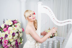 Beautiful young girl portrait in spring flowers playing the harp Stock Photography
