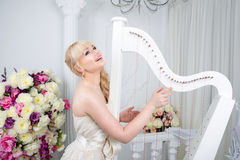 Beautiful young girl portrait in spring flowers playing the harp Royalty Free Stock Images