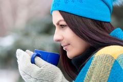 Beautiful young girl portrait on winter background. A charming young lady walking in a winter forest. Attractive woman with Cup. Royalty Free Stock Image
