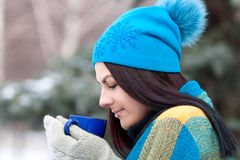 Beautiful young girl portrait on winter background. A charming young lady walking in a winter forest. Attractive woman with Cup. Stock Photo