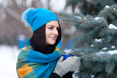 Beautiful young girl portrait on winter background. A charming young lady walking in a winter forest. Attractive woman with Cup. Stock Photos