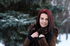 Beautiful young girl portrait on winter background. Charming young lady walking in a winter forest. Attractive woman posing. Stock Photography