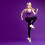 Beautiful young girl in a pose runner. Studio background, purple royalty free stock image
