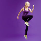 Beautiful young girl in a pose runner. Studio background, purple Royalty Free Stock Photos