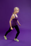 Beautiful young girl in a pose runner. Studio background, purple Stock Photo
