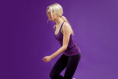 Beautiful young girl in a pose runner. Studio background, purple Stock Image