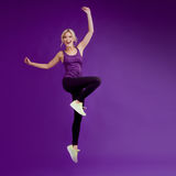 Beautiful young girl in a pose runner. Studio background, purple. Happy jumping Royalty Free Stock Photo