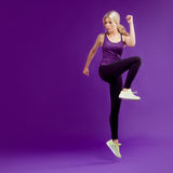 Beautiful young girl in a pose runner. Studio background, purple. Happy jumping stock photos