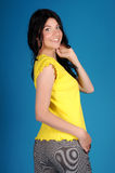 Beautiful young girl posing on a blue background stock photography