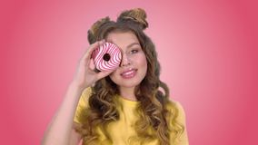 Beautiful young girl posing with a donut winks and smiling looking at the camera on a pink background. Beautiful young girl in a yellow shirt posing with a donut stock footage