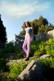 Beautiful young girl posing outdoor. Fashionable beautiful young woman posing outdoor in park, summer day. Girl wearing pink jeans. Brunette lady Stock Photo
