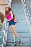 Beautiful young girl posing on steps in a city background Royalty Free Stock Photo