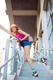 Beautiful young girl posing on steps in a city background Royalty Free Stock Image