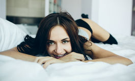 Beautiful young girl posing on a white bed Royalty Free Stock Photo