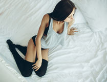 Beautiful young girl posing on a white bed Royalty Free Stock Photos