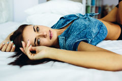 Beautiful young girl posing on a white bed Royalty Free Stock Photography