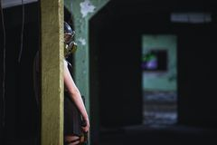 Beautiful, young girl post apocalypse girl stand in abandoned factory with gas mask and machine gun Royalty Free Stock Photos