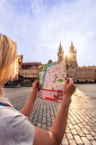Beautiful young girl in Prague looks at the city map. Stock Image