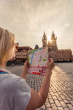 Beautiful young girl in Prague looks at the city map. Royalty Free Stock Photos