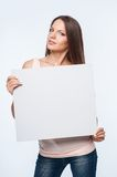 Beautiful young girl is presenting white frame Royalty Free Stock Photos