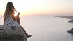 Beautiful young girl in pretty sundress is sitting on the rock by the sea, admiring the sunset, waving carefree her leg stock video
