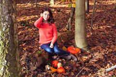 Beautiful young girl with pumpkin and corn in autumnal forest Royalty Free Stock Images