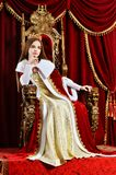Beautiful young girl Queen. On the throne royalty free stock photos