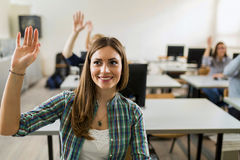 Beautiful young girl raising hand in classroom Stock Photo