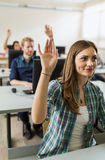 Beautiful young girl raising hand in classroom Stock Photography